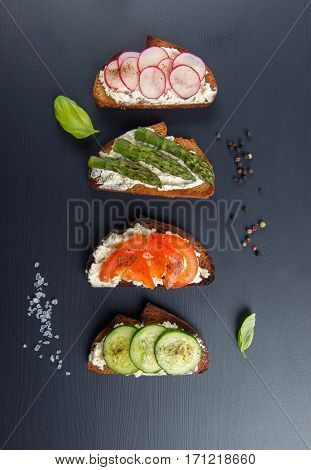 Four different sandwiches on black board