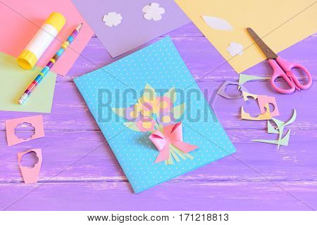 Creating a greeting card for mom. Step. Card with flowers made of colored paper. Materials for kids art on a wooden table. Gift idea for Mother's day, birthday, March 8 for preschool children to make