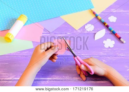 Small child creates a greeting card for mom. Step. Child holds scissors and cuts a flower from paper. Materials for creative art on a wooden table. Crafts idea for Mother's day or birthday or March 8