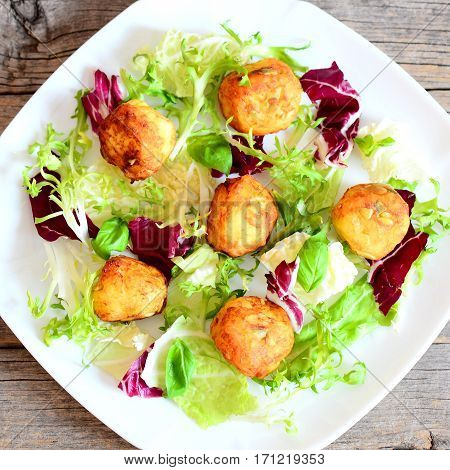 Fried mashed potato balls with pumpkin seeds served with fresh lettuce and basil on a plate and on wooden background. Easy and tasty potato balls recipe. Top view