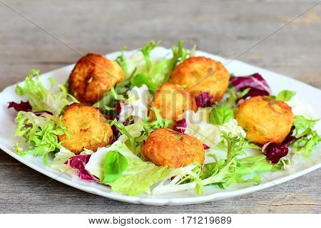 Fried mashed potato balls with pumpkin seeds served with fresh lettuce and basil on a plate and on wooden background. Quick and tasty potato balls recipe. Closeup