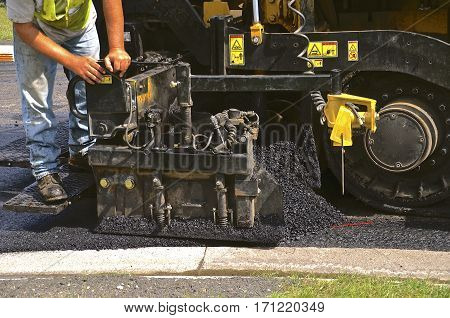 Hot steamy asphalt is being laid on a street in a road construction project.