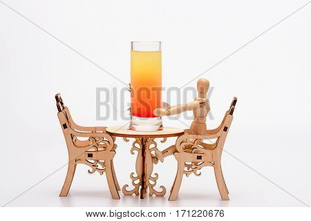 alcohol cocktail in glass: sex on the beach on little decorative table with chairs and wooden model of human isolated on white background side view