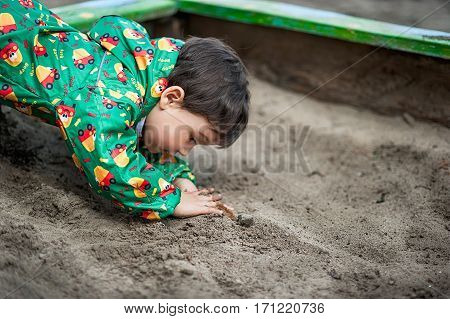 little boy in green raibcoat playing with sand in sandbox
