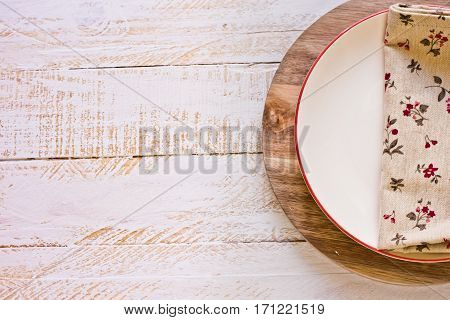 Off-white empty plate with red board on round cutting board linen floral napkin white plank wood background Provence style kitchen interior minimalistic kinfolkflat lay copyspace