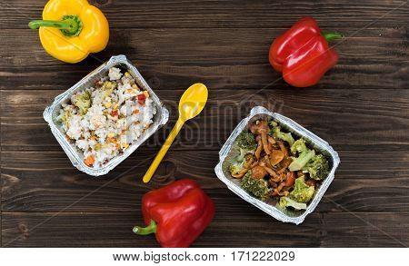 Time for dinner. Yellow spoon lying between two boxes stewed rice with vegetables and well-done broccoli with mushrooms are packed in foil box