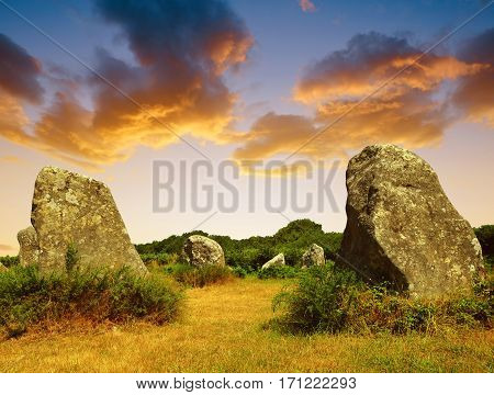 Megalithic monuments menhirs in Carnac at sunset - Brittany, France