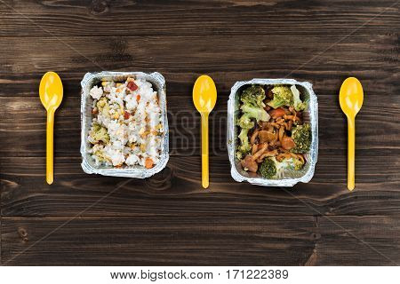 Sort order. Yellow spoons lying parallel to each other on the table, stewed rice with vegetables and well-done broccoli with mushrooms are packed in foil box waiting for dinner