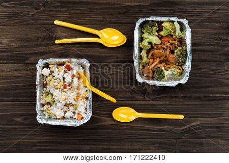 Break in office. Two foil boxes containing stewed rice with vegetables and well-done green broccoli with mushrooms lying on the wooden table near plastic spoons