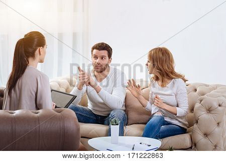 You are wrong. Angry nice young woman looking at her husband and gesticulating while saying something to him