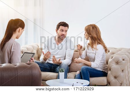 Family conflict. Angry emotional young couple looking at each other and gesticulating while having a quarrel