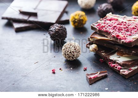 Sweet and treat, junk unhealthy food. Assortment of chocolate bar and praline truffle on black moody grunge table. Copy space background