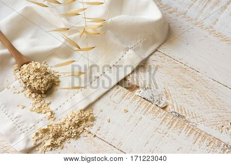 Dry oatmeal flakes on a wooen spoon over a white linen cloth plant twig plank wood background clean eating rustic health concept beauty skin care top view copyspace