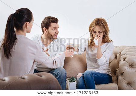 I need to calm down. Sad cheerless woman holding a tissue and taking a glass with water while trying to calm down