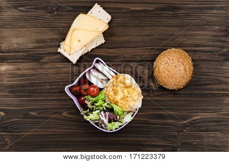 Lunch for student. Little bun standing near big lunch box, two pieces of bread with slice of cheese lying above this box on the table