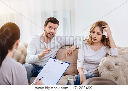 Problems in the relationships. Nice cheerless young man sitting next to his wife and telling the psychologist about their family problem while having a psychological session