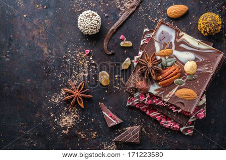 Sweet and treat, junk unhealthy food. Assortment of chocolate bar and praline with spices and nuts on black moody grunge table. Top view flat lay overhead, copy space background