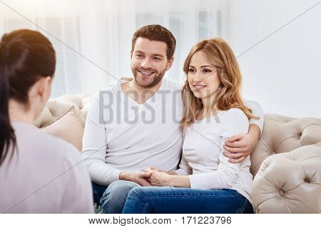 Happy couple. Delighted happy positive man looking at the psychologist and smiling while hugging his wife