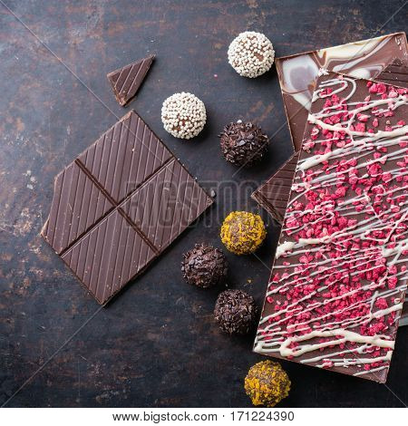 Sweet and treat, junk unhealthy food. Assortment of chocolate bar and praline truffle on black moody grunge table. Top view flat lay overhead