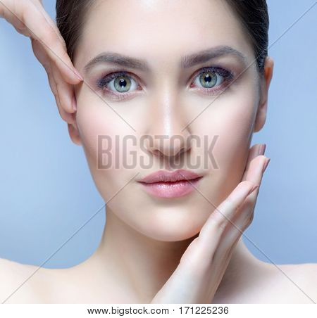 closeup portrait of attractive young  caucasian woman brunette  on blue background studio shot lips face  head and shoulders skin hands nails looking at camera eyes