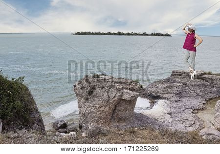 horizontal image a slender caucasian woman and her little white dog standing on a small rock cliff  posing for the camera looking across the beautiful green tinged lake in the summer time.