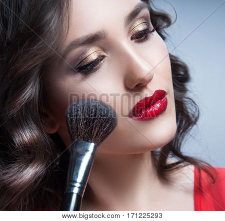 beauty closeup portrait of attractive young caucasian woman brunette on blue background studio shot red lips face closeup skin hair head and shoulders brush
