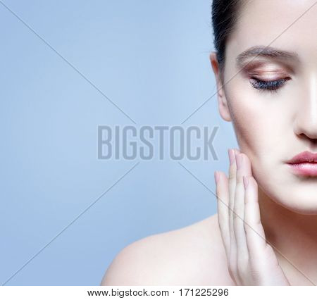 closeup portrait of attractive young  caucasian woman brunette  on blue background studio shot lips face  head and shoulders skin hands nails eyes closed