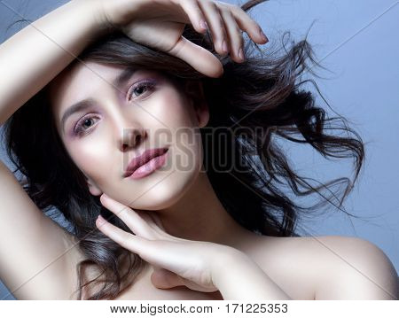 closeup beauty portrait of attractive young caucasian woman brunette on blue background  studio shot lips face hair head and shoulders looking at camera hands makeup