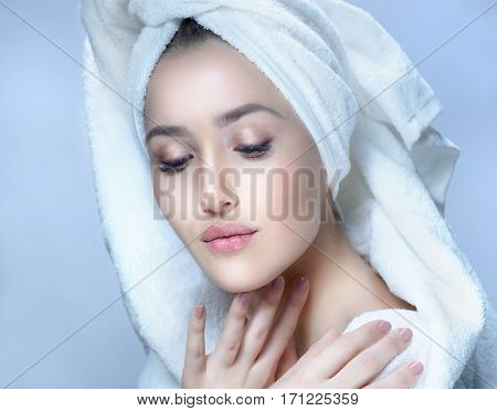 closeup beauty portrait of attractive young caucasian woman brunette on blue background studio shot lips  face head and shoulders skin care towel tube spa