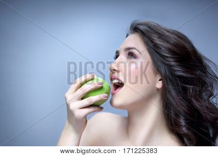 beauty portrait of attractive young caucasian smiling woman brunette on blue background studio shot eating green apple teeth healthy eating looking up