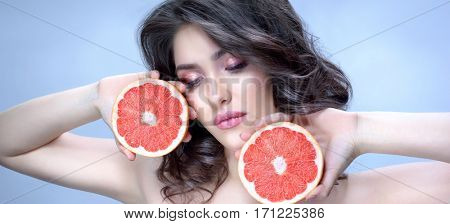 Beauty Brunette Model Woman with Perfect Makeup. Fresh Skin Look. Beauty Girl's Face isolated on blue background. Grapefruit Slice in hands. Healthy eating concept