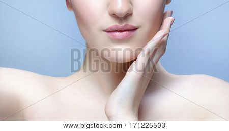 closeup portrait of attractive young  caucasian woman on blue background studio shot lips face  skin hands nails neck