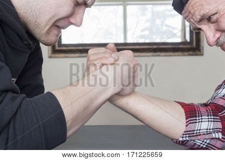horizontal close up image of a caucasian father and teenage son arm wrestling.