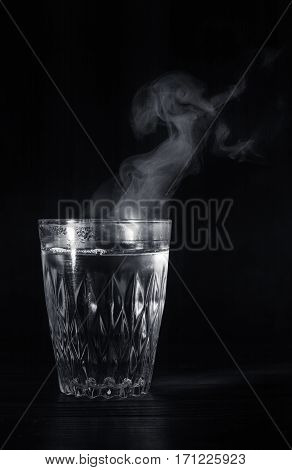 Transparent Glass Cup With Swell The Boiling Water Into It. The Vapor From The Top. Black Background
