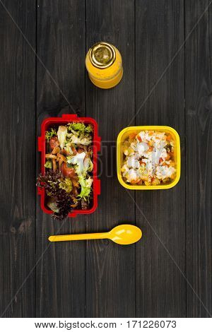 Student lifestyle. Flat lay picture of orange juice in bottle standing near lunch boxes, yellow spoon is situated next to salad box