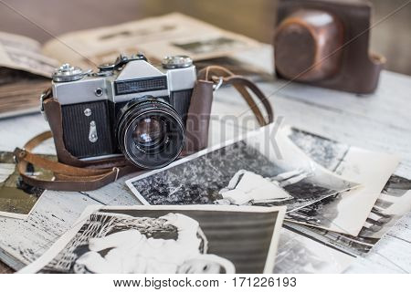 An old camera with vantage family photos and picture album on a white wooden background.