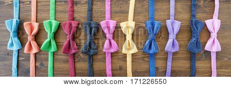 Variety of colorful bow tie on rustic wooden background