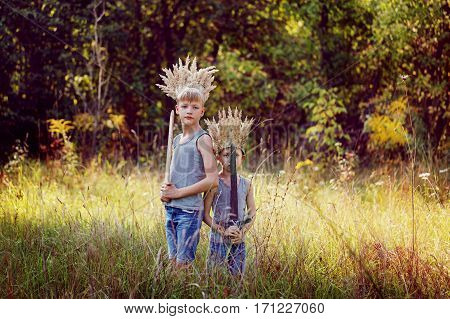 Portrait Two Brothers have a crown from dry grass on the head and swords in hands. Joy and play concept.