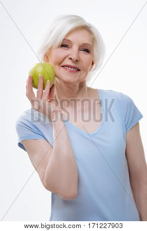 Just eat it. Beautiful aged female wearing blue tee shirt expressing positivity while holding green fruit