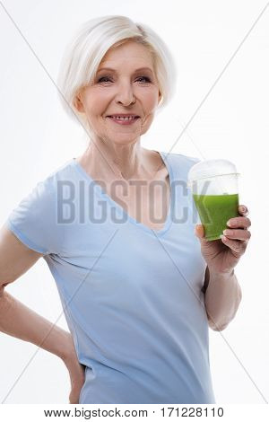 Drinkable vitamins. Positive delighted aged woman wearing blue tee shirt putting her right hand on the waist while holding smoothie in left hand