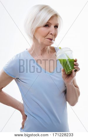 Great example. Happy woman standing in semi position holding a glass in the left hand while drinking smoothie, isolated on white background