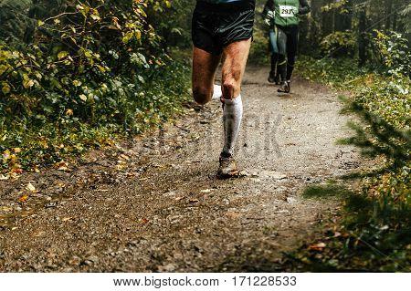 male runner runs marathon forest trail feet in mud