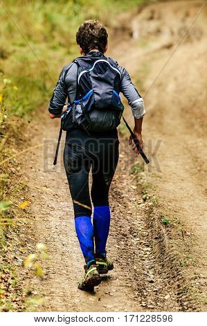back woman with backpack and walking sticks runs trail
