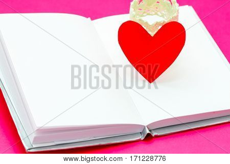 Single Simple Of Red Paper Heart Over White Opened Book On Pink Background, Valentine Day Concept