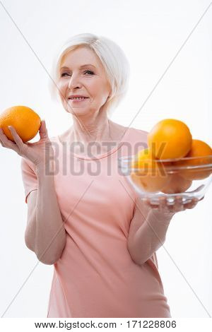 Citrus fruits. Positive amazing woman wearing T-shirt keeping her arms bent in elbow while demonstrating oranges