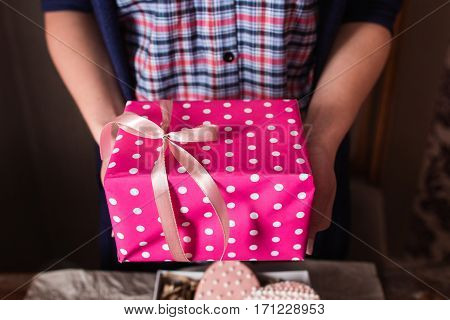 Unrecognizable woman holding pink gift box. Bright rosy present package in female hands, free space. Holiday, surprise, joy, fun concept