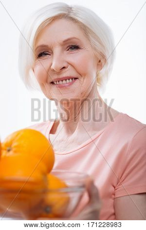 Happy old age. Happy smiling female wearing pink tee shirt holding bowl with oranges looking at camera, isolated on white background