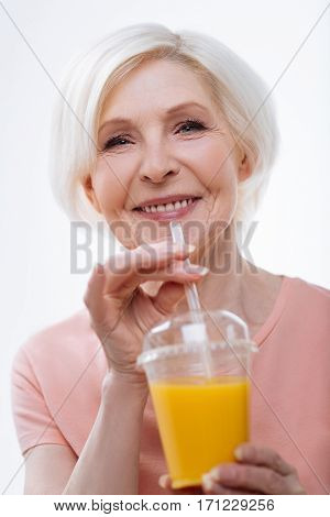Sweet juice. Portrait of healthy aged woman wearing pink tee shirt posing on camera while going to drink fresh orange juice, isolated on white background