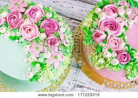 Two celebratory cake with flowers rose on a white wooden background.