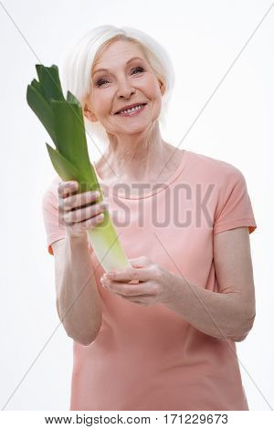 Healthy vegetables. Sincere aged female feeling happiness holding big green leek, standing over white background